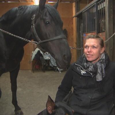 Lyne Joly est tout sourire en prenant la pose aux côtés de son cheval. dans son écurie.