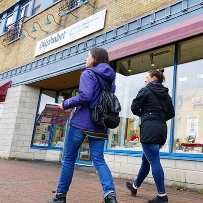 Deux personnes marchent devant une librairie, à Rimouski.