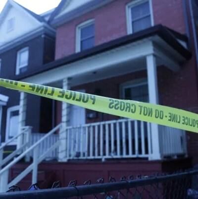 Des maisons résidentielles avec un bandeau de la police devant.