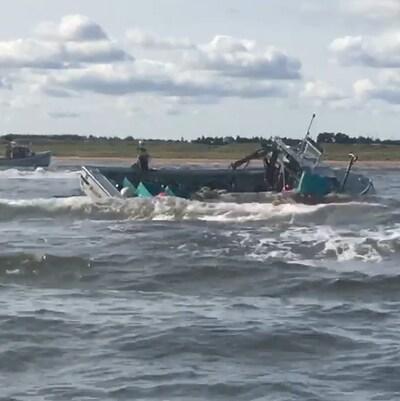 Des contenants s'échappent du bateau ballotté par les vagues.