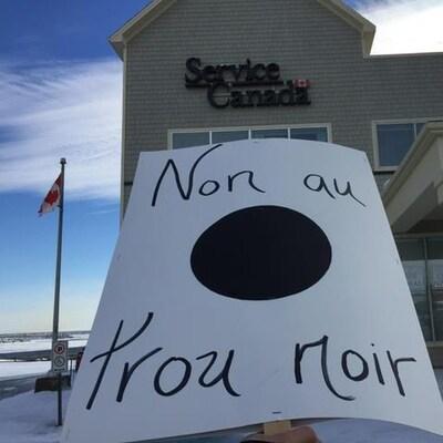 Affiche « Non au trou noir » devant le bâtiment de Service Canada de Cap-aux-Meules.