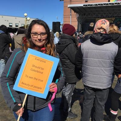 Une jeune femme présente à la marche tenait une affiche stipulant que « tout le monde devrait être « daltonien » pour voir la beauté des gens (et non la couleur de la peau) »