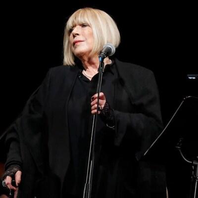 Marianne Faithfull, toute vêtue de noir, est sur scène et tient le pied d'un mi.