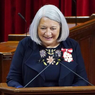 Une dame est postée derrière un lutrin et sourit.