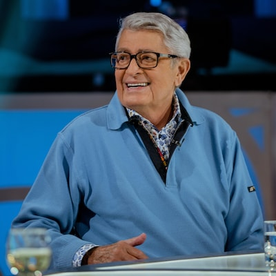 L'homme habillé d'un chandail bleu est assis et se tourne en souriant vers quelqu'un.