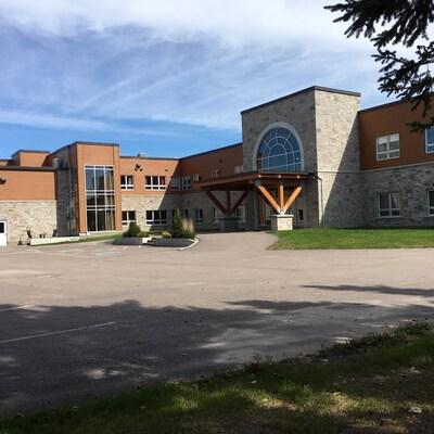 Le bâtiment est en pierre et en bois. Il y a un grand stationnement.