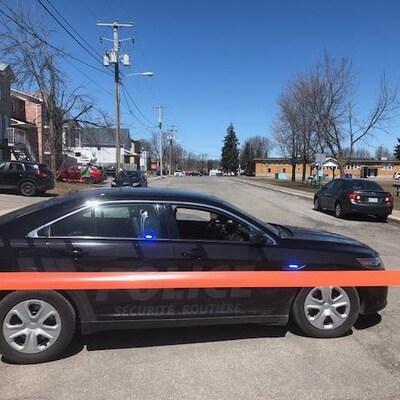 Une voiture noire du Service de police de Gatineau et un périmètre de sécurité qui ferme une rue.