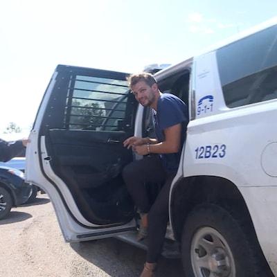 L'homme sort d'un véhicule de la Gendarmerie royale du Canada escorté par un policier.