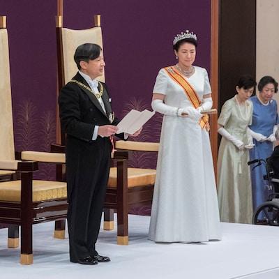 Un homme, accompagné d'une femme sur un podium, prononce un discours.