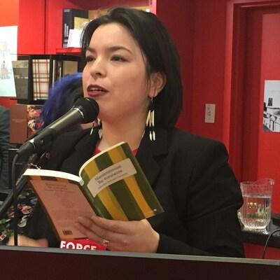 Natasha Kanapé-Fontaine au micro pour première une lecture publique lors du lancement de son livre Nanimissuat Île-tonnerre à la librairie Gallimard de Montréal.
