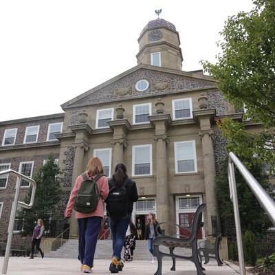 En avant-plan, des étudiantes se dirigent vers un des édifices de l'Université Dalhousie.
