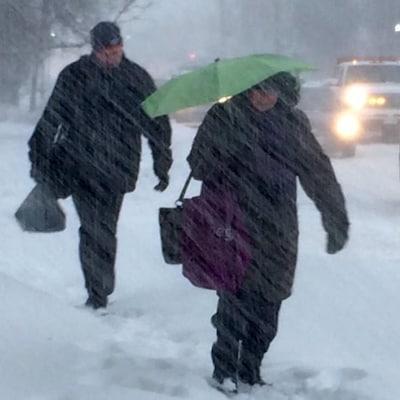 Des gens marchent sur un trottoir et des véhicules circulent dans une rue enneigée