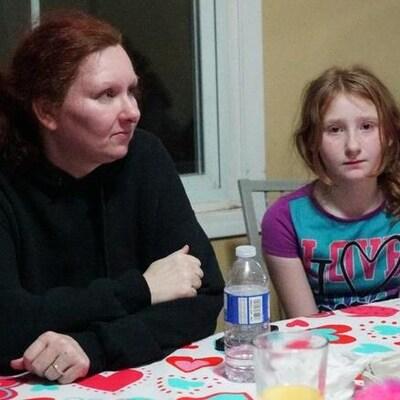 Une femme et une fille sont assises à une table dans la salle à manger d'une résidence.