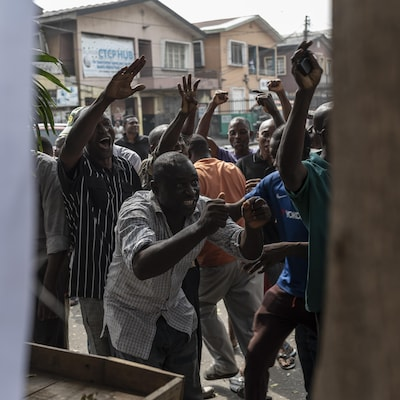 Des hommes nigérians lèvent les bras dans les airs devant un kiosque à journaux dans une rue.