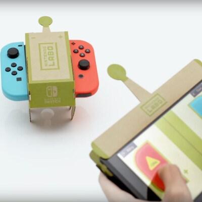 Une petite voiture en carton sur laquelle sont installées les deux manettes de la Nintendo Switch.