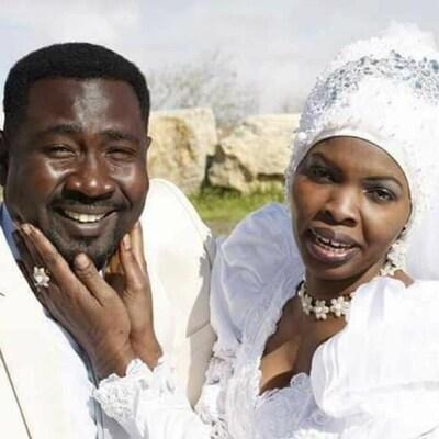 Le couple souriant, tout vêtu de blanc, en tenue de mariage.
