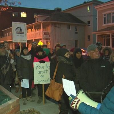 """Plusieurs personnes portent des pancartes avec des slogans dont """"Pour le droit au logement"""", et """"Personne n'est à l'abri""""."""