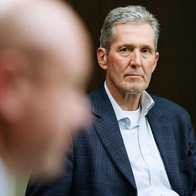 Le premier ministre Brian Pallister, vu de face, regarde Brent Roussin qui est au premier plan sur la photo, et dont le visage de profil est hors focus.