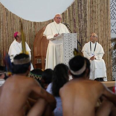 François prend la parole au micro, avec des indigènes torse nu devant lui.