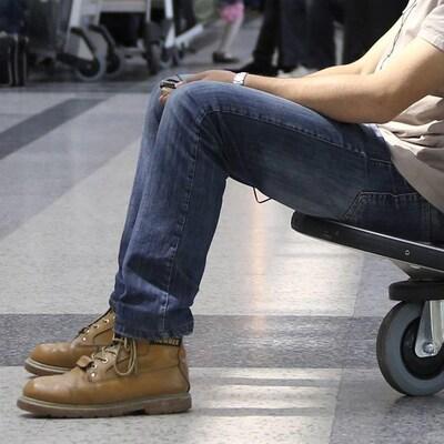 Un homme assis dans un chariot à bagages attend à l'aéroport.