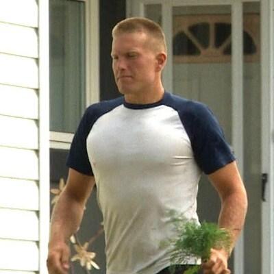 Patrik Mathews devant une maison.