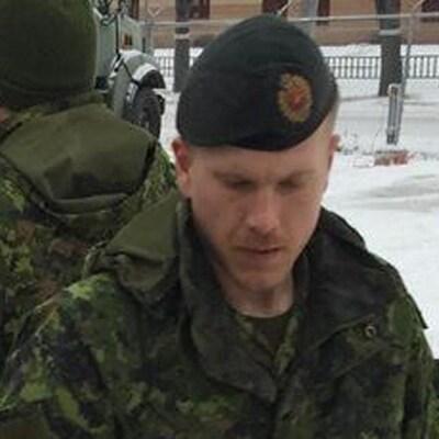 Plan serré de Patrik Mathews vêtu de l'uniforme de l'armée. Il est dehors en hiver. L'arrière-plan montre un autre soldat de dos et des véhicules de l'armée.