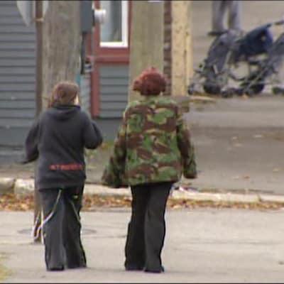 Deux enfants traversent la rue dans un quartier pauvre de Saint-Jean au Nouveau-Brunswick.