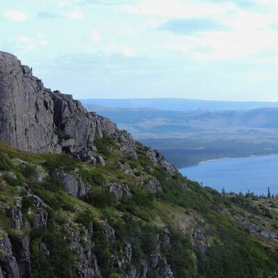 On voit une colline des monts Otish et, au loin, un lac.