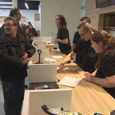 Au comptoir en bois clair d'un magasin de cannabis, les clients attendent pendant que les vendeurs s'empressent d'encaisser les ventes.