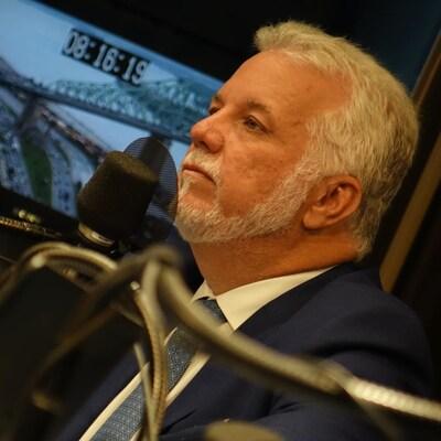 Philippe Couillard, devant un micro, dans un studio de radio.