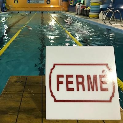 Une affiche indique fermé au bout d'un corridor de piscine sportive.