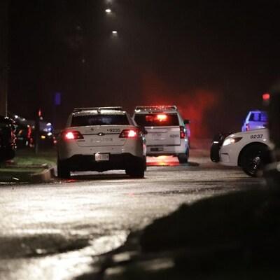 Plusieurs voitures de police dans la rue des Bolets à Québec la nuit.
