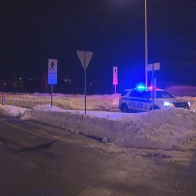 Une voiture de police stationnée dans la rue l'hiver