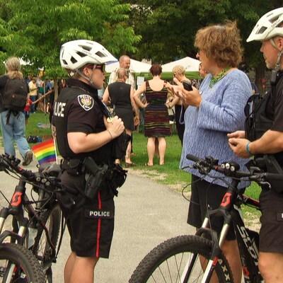 Des policiers à vélo avec un drapeau arc-en-ciel sur leur vélo