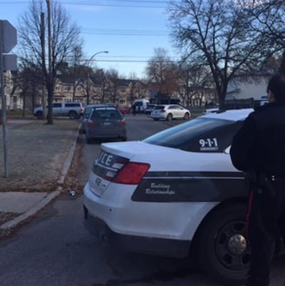 Un policier est debout devant une voiture de police stationnée dans la rue.
