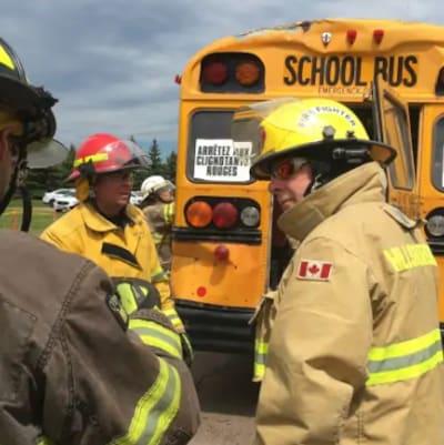 Des pompiers discutent devant un autobus d'écoliers.