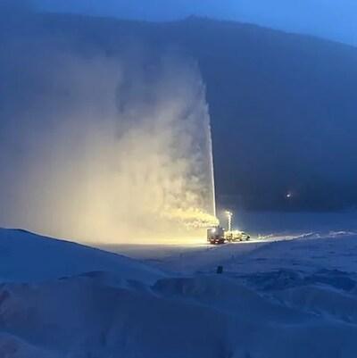 Une machine souffle de la neige en l'air lors de la construction d'un pont de glace près de Dawson.