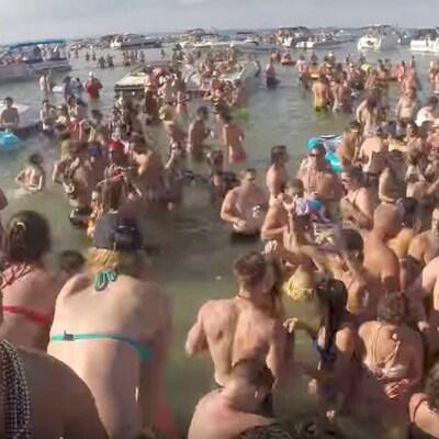 Des dizaines de personnes font la fête dans un lac, l'été.