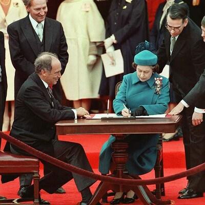 Une femme vêtue de bleu, assise à une table signe un document. Elle est entourée du premier ministre, lui aussi assis près d'elle, et d'autres personnes qui se tiennent debout et sourient, dans un cadre officiel.