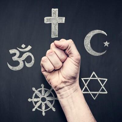 Un poing serré devant un fond noir où se trouvent les symboles de cinq religions.