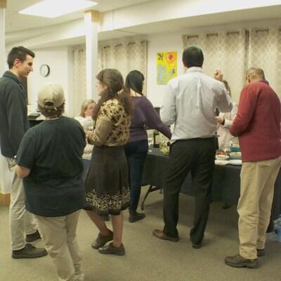 Vue sur huit personnes qui sont debout dans une salle. Elles discutent ensemble autour d'une table sur laquelle il y a de la nourriture.