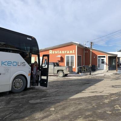 Un autocar stationné devant le restaurant Le héron.