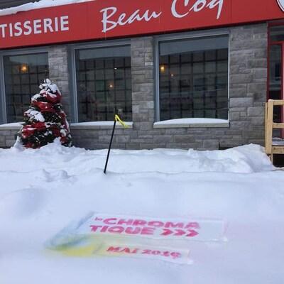 Un logo de la Chromatique avec la date mai 2019 est dessiné dans la neige devant un restaurant.