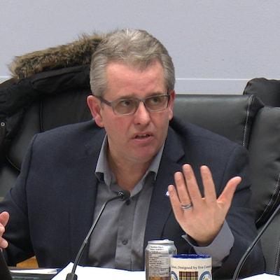 Le conseiller municipal de Timmins, Rick Dubeau, est assis derrière son micro et s'adresse au maire Steve Black lors d'une réunion du conseil municipal.
