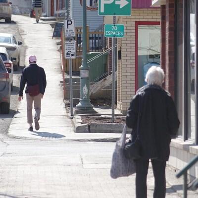Des personnes marchent sur un trottoir de Rivière-du-Loup.
