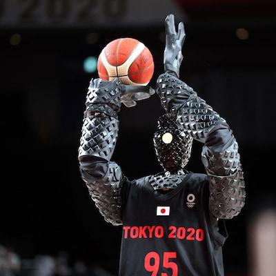 Un robot humanoïde de couleur noire mesurant 210 cm (près de 7 pieds) tient un ballon de basketball dans une main et s'apprête à lancer.