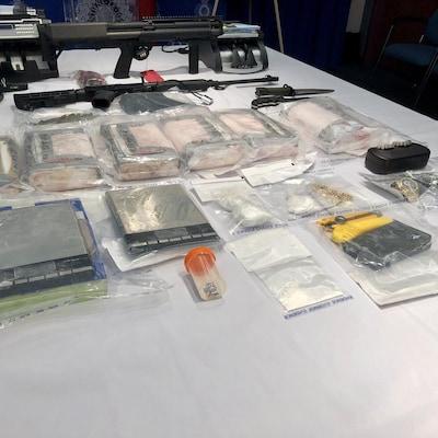 Des armes à feu, des appareils électroniques, des bijoux et de la drogue en sachets exposés sur une table.