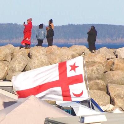 Des gens près de l'eau, sur des rochers, et un drapeau mi'kmaq planté devant les rochers.