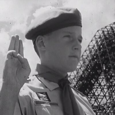 Le jeune garçon qui regarde droit devant lui fait le salut scout avec ses doigts.