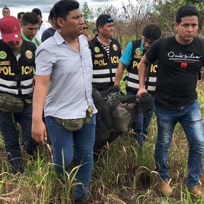 Des policiers habillés en civil, mais certains avec une veste sur laquelle il est inscrit POLICIA, transportent le corps d'un homme décédé enveloppé dans une toile. Ils sont dans un champs avec des herbes hautes.